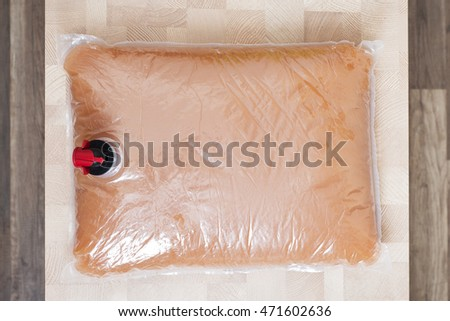 Plastic bag with tap full of apple juice on the wooden table