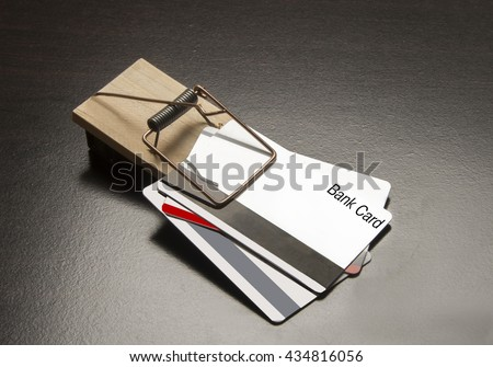 Plastic bank cards in a metal trap/Credit Trap/Plastic material  caught in a mouse trap. - stock photo
