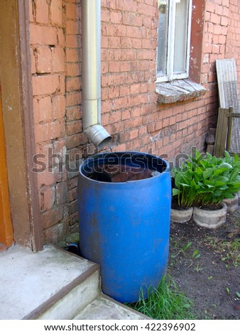 Plastic barrel under drain pipe full with collected rain water.                                - stock photo