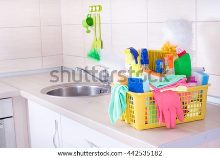 Plastic basket full of cleaning supplies and equipment on kitchen countertop - stock photo