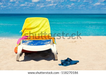 Plastic bed covered by colorful towels and a pair of flip flops on the beautiful beach of Varadero in Cuba - stock photo