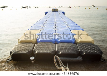 Plastic blue rotomolding jetty in the empty sea against blue sky. - stock photo