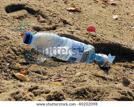 plastic bottle and dust on beach sand