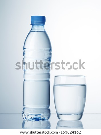 plastic bottle and glass of water - stock photo