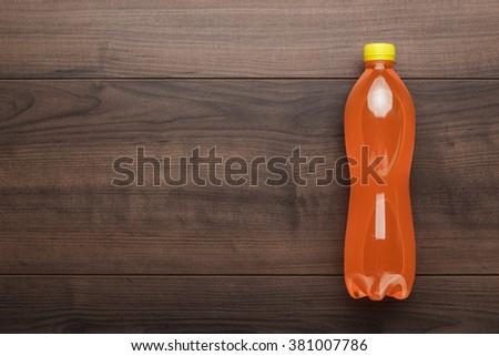 plastic bottle of orange soda on wooden table - stock photo