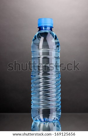 plastic bottle of water on grey background - stock photo