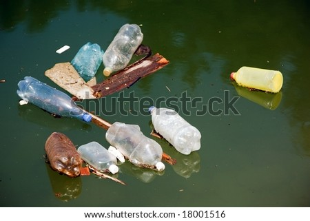 plastic bottle pollution on water, focus on the front - stock photo