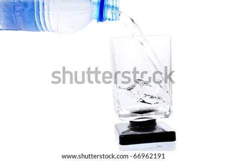 Plastic bottle pouring water into a square glass isolated on white