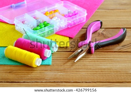 Plastic box with colorful beads, a set of thread, needle, pliers, sheets of felt on wooden background. A set of tools and materials for children's art and crafts  - stock photo