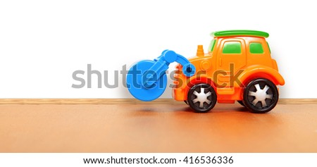 plastic car on the floor in a playroom - stock photo