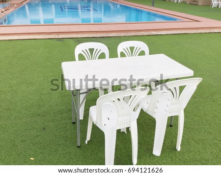 Plastic chairs and a table gardens furniture over a swimming pool. Plastic Garden Furniture Stock Images  Royalty Free Images