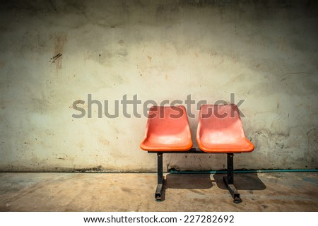 Plastic chairs on the background wall - stock photo