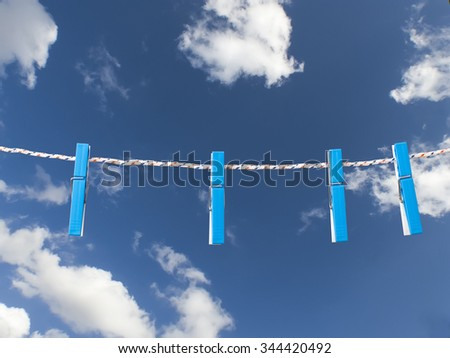 Plastic clothes pegs on rope against blue sky - stock photo