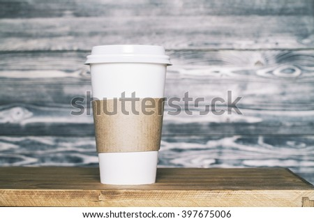 Plastic coffee cup on wooden background. Mock up - stock photo