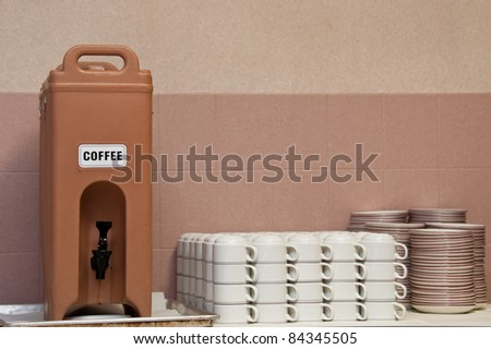 Plastic coffee dispenser sitting on a dirty drip pan. White coffee mugs and snack plates are also shown. - stock photo