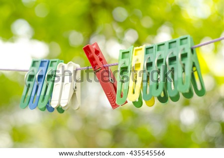 Plastic color clothespin hanging on rope, isolated on green bokeh background. Close-up, outdoor, depth of field. Colorful clothes pegs set. - stock photo