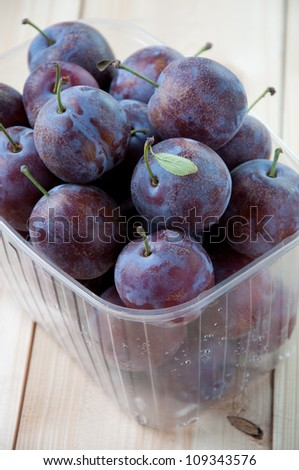 Plastic container full of freshly harvested organic plums