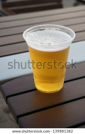 Plastic cup of beer standing on the wooden table - stock photo