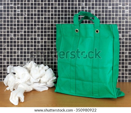 Plastic disposable bags and environmentally friendly re- usable bags with dark mosaic tile background - stock photo