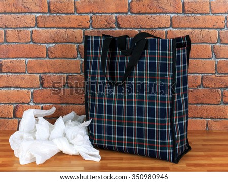 Plastic disposable bags and environmentally friendly  re- usable tartan bag with a red brick wall background - stock photo