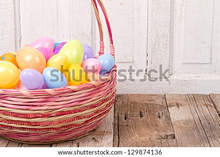 Plastic Easter Eggs In Basket On Rustic Wooden Background