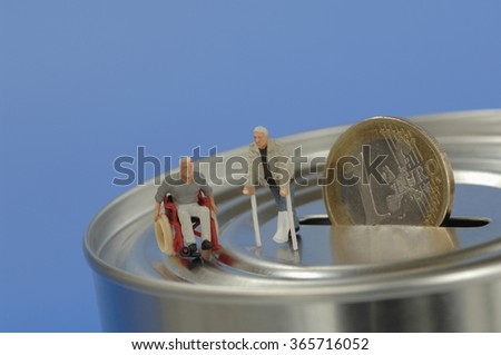 Plastic figurines, in wheelchair and with crutches on money box - stock photo