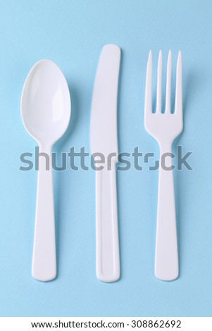 Plastic Fork Spoon and Knife on Blue Background - stock photo