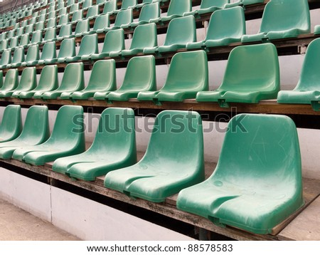 plastic green old chairs in stadium - stock photo