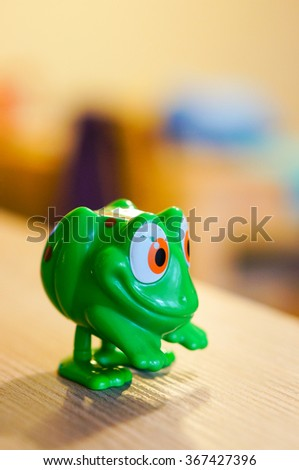 Plastic green toy frog on wooden table