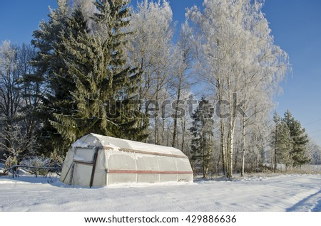 plastic greenhouse hothouse in winter farm covered hoarfrost snow - stock photo