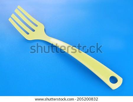 Plastic kitchen utensil on blue background - stock photo