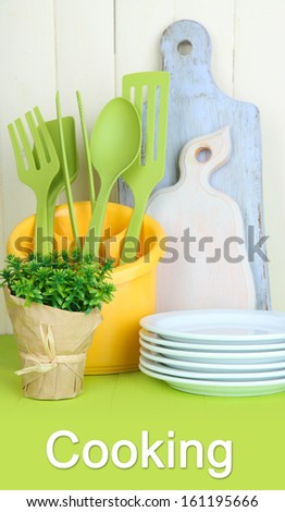 Plastic kitchen utensils in cup on wooden table - stock photo