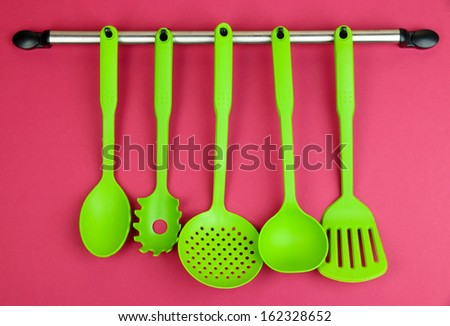 Plastic kitchen utensils on silver hooks on red background - stock photo