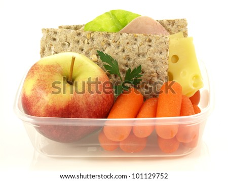 Plastic lunch box with fruits and vegetables - stock photo