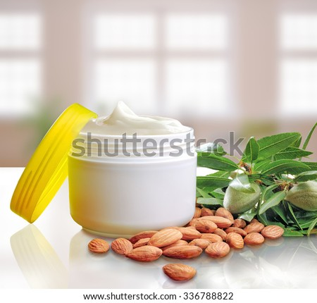 Plastic open jar with facial or body almond moisturizer on white table. Front view. Square composition. Windows background. - stock photo