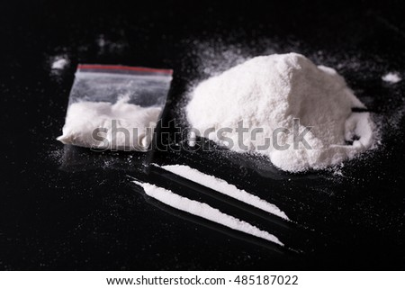Plastic packet, two lines and pile of cocaine on black background, closeup