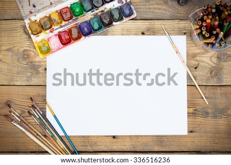 Plastic paint palette with paint and brushes on wooden table - stock photo