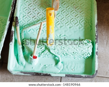plastic paint tray with paint brushes and paint roller
