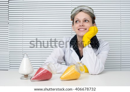 Plastic pellets. Female researcher sitting at a desk in the lab. looking up - stock photo