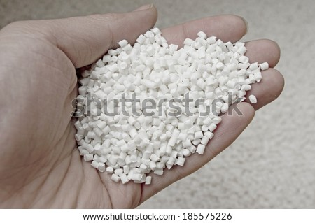 Plastic pellets in holding hand, raw material of injection molding.