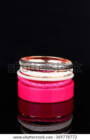 Plastic Pink bracelet isolated on black background. - stock photo