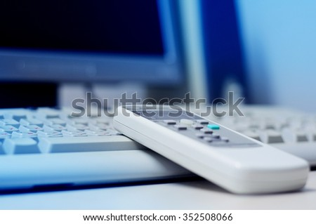 Plastic remote control of air conditioning on computer keyboard in modern office with blue tone business color  - stock photo