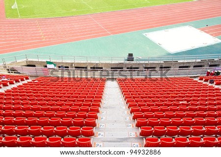 plastic seats in very big, empty stadium - stock photo