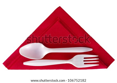 Plastic spoon and fork on red triangle serviette aka napkin, isolated
