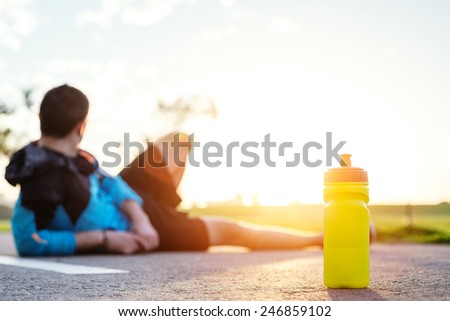 plastic sport bottle with water and blurred tired sportsman in shorts lying on the road in park and looking at sunset