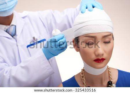 Plastic surgeon bandaging head of glamorous Chinese woman - stock photo