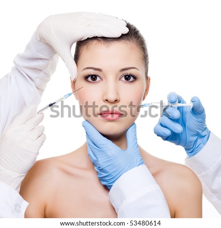 Plastic surgeons giving injection in female skin of eyes and lips - isolated white - stock photo