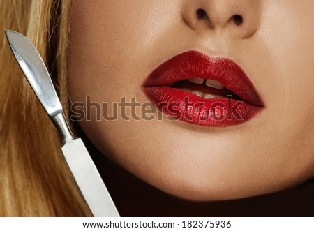 Plastic surgery tool near young woman face  - stock photo