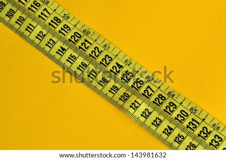 Plastic tape measure inches and centimeters. Abstract numbers yellow background.
