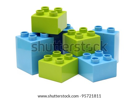 Plastic toy blocks on white. Focus on near edge of bricks with selective focus. - stock photo